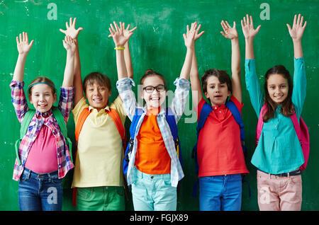 Happy pupils raising hands against blackboard - Stock Photo