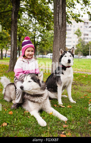 little cute girl playing with husky dog outside in green park - Stock Photo