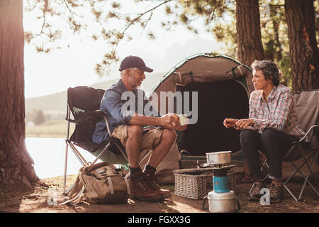 Portrait of happy mature campers enjoying coffee by the lake. Mature couple relaxing at their campsite. - Stockfoto