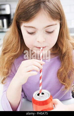 Young Girl Drinking Can Of Soda Through Straw - Stock Photo