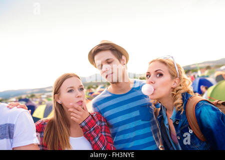 Teenagers at summer music festival blowing buble gums - Stock Photo