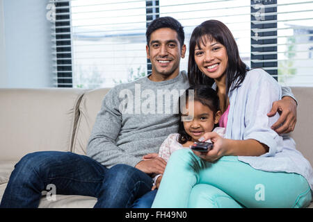 Smiling family watching tv on the sofa - Stock Photo