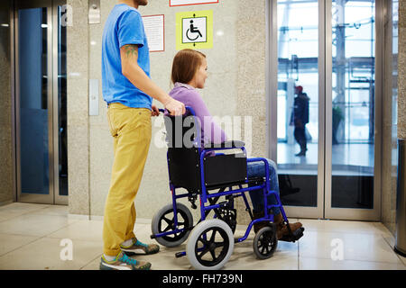 Guy and his girlfriend in wheelchair waiting for elevator - Stock Photo