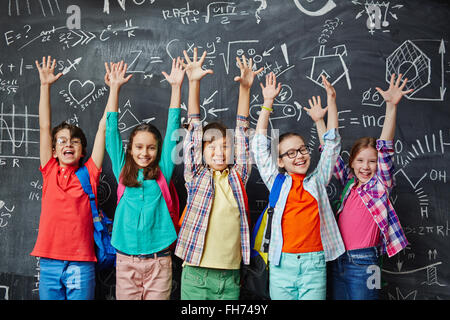 Ecstatic learners raising hands against blackboard - Stock Photo