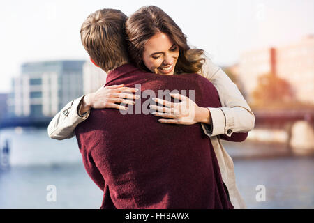 Germany, Berlin, happy young couple hugging at River Spree - Stock Photo
