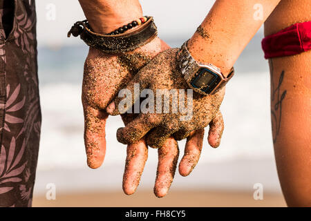 Close-up of couple holding sandy hands - Stock Photo