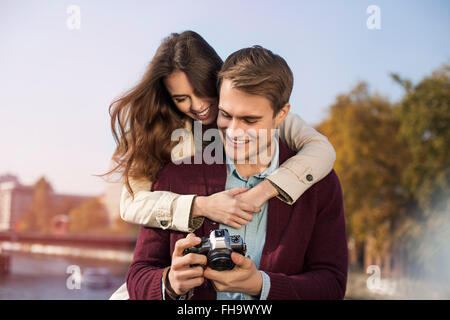 Germany, Berlin, happy young couple looking at camera at bank of River Spree - Stock Photo