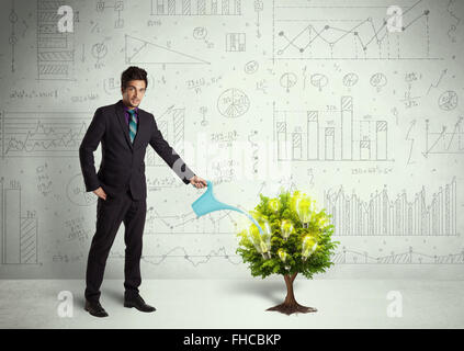 Business man pouring water on lightbulb growing tree - Stock Photo