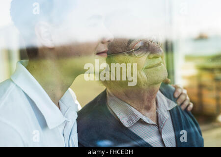 Senior man and young man looking together through window - Stock Photo