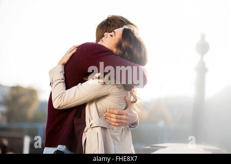 Germany, Berlin, young couple hugging - Stock Photo