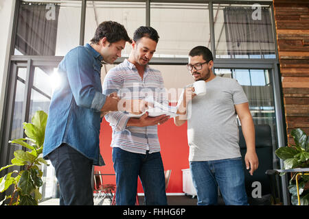 Group of businesspeople discussing paperwork in office. Three young men meeting in office. - Stock Photo