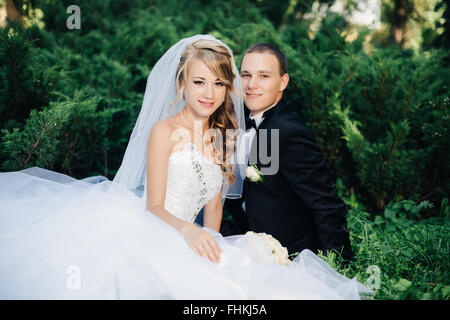 Bride sit together with groom on green grass park - Stock Photo