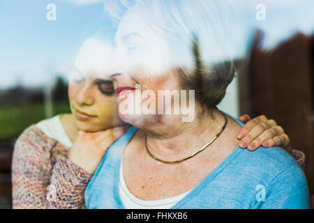 Young woman and senior woman with closed eyes behind windowpane - Stock Photo