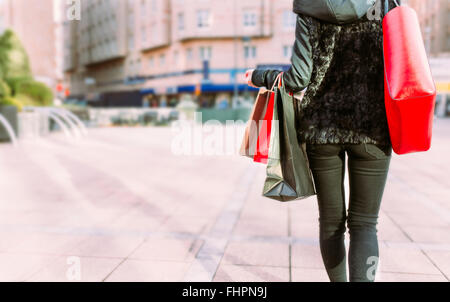 Back view of young woman carrying shopping bags - Stock Photo