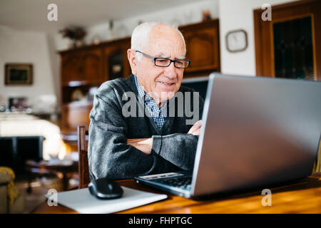 Portrait of smiling senior man with laptop at home - Stock Photo