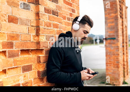 Portrait of young man listening music with headphones - Stock Photo