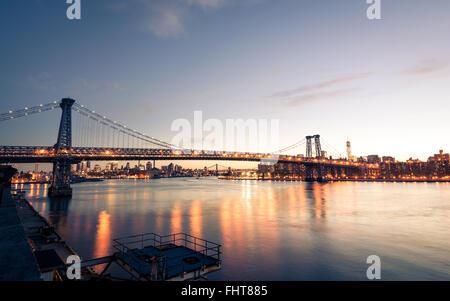 Reflected light on East River under Manhattan Bridge at sunset - Stock Photo