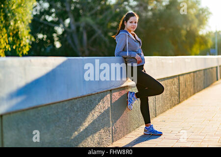 Beautiful woman resting in city after jogging in the morning - Stock Photo