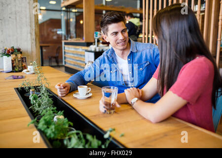 Happy young couple in restaurant waiting for food and talking - Stock Photo