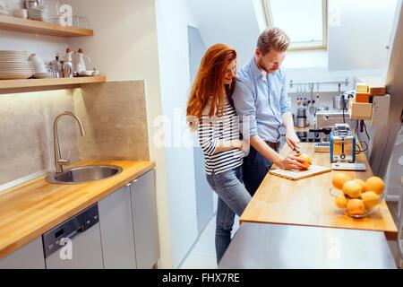 Couple making orange smoothie in kitchen from fresh oranges - Stock Photo