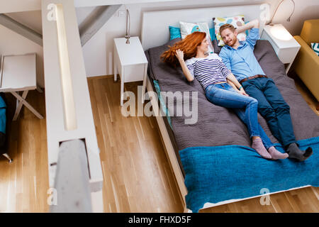 Beautiful couple resting on bed in a modern apartment - Stock Photo