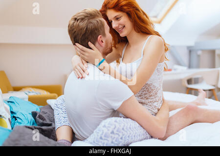 Romantic couple in love lying on bed and being passionate - Stock Photo