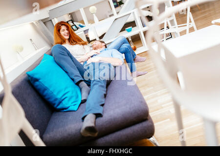 Couple cuddling in beautiful interior living room while lying on sofa - Stock Photo