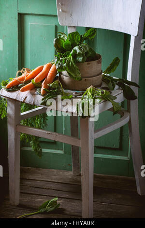 Bunch of fresh spinach and carrots on old white wooden chair with green wooden wall at background. - Stock Photo