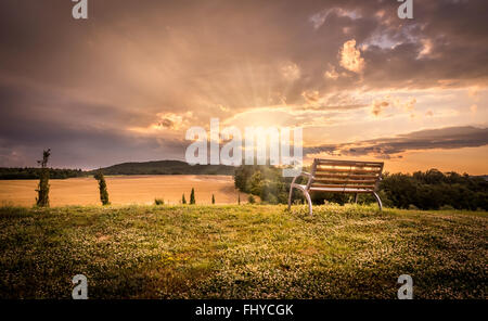 Beautiful sunset landscape with lonely bench in the foreground - Stock Photo