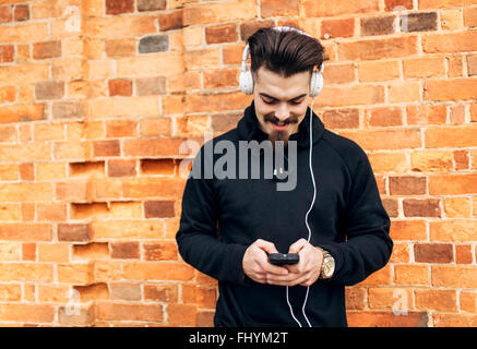 Portrait of young man in front of brick wall listening music with headphones - Stock Photo