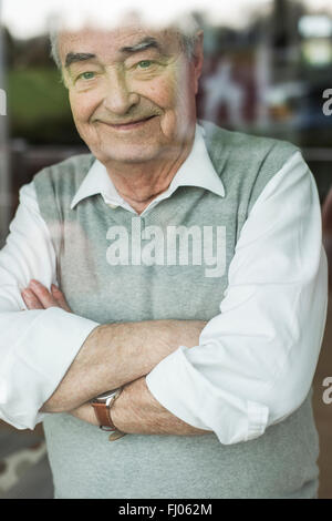 Portrait of smiling senior man with crossed arms looking through window - Stock Photo