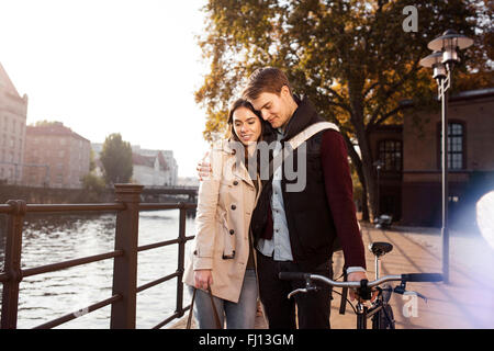 Germany, Berlin, young couple hugging at River Spree - Stock Photo