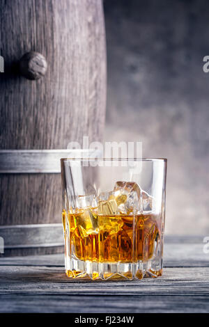 Round glass of whiskey with ice cubes against the background of wooden barrels - Stock Photo