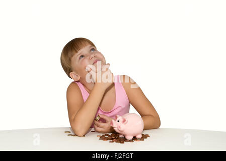 Thoughtful girl with piggy bank and euro coins on the table isolated - Stock Photo