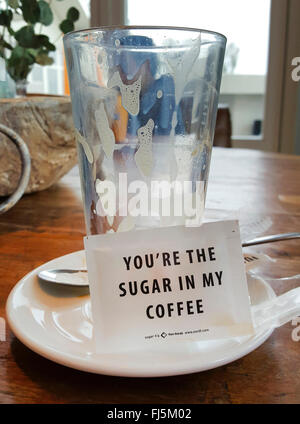 drunk up glass and sachet of sugar with the writing 'You're the sugar in my coffee' - Stockfoto