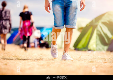 Unrecognizable teenage couple, tent festival, sunny summer, legs - Stock Photo