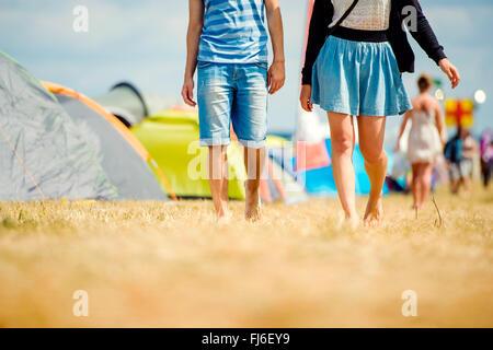 Unrecognizable teenage couple, tent festival, sunny summer, legs - Stock Photo