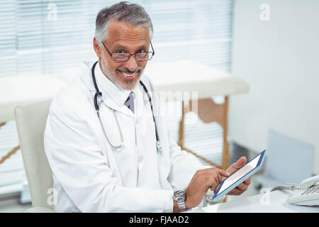 Doctor using digital tablet at clinic - Stock Photo