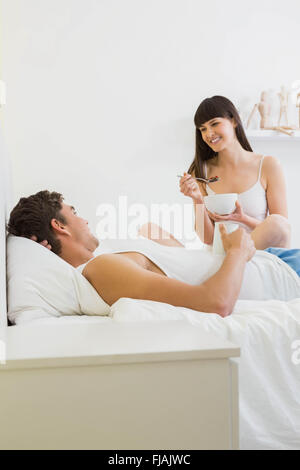 Young couple having breakfast on bed - Stock Photo