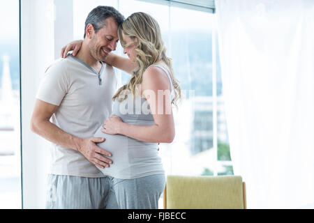 Man holding pregnant womans stomach - Stock Photo