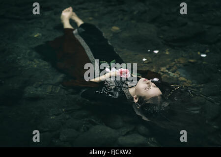 Beautiful floating dead woman in water . Ophelia conceptual - Stock Photo