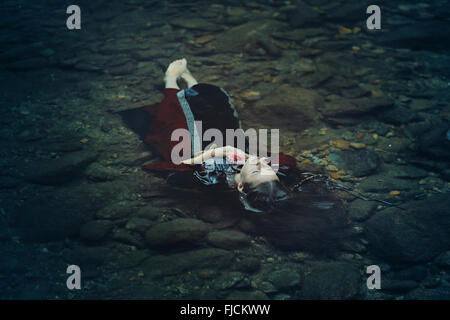 Beautiful floating woman in dark water . Ophelia conceptual - Stock Photo
