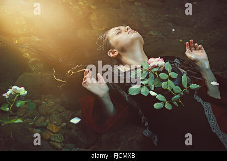 Woman in dark water stream and soft sunlight . Romantic and tragedy - Stockfoto