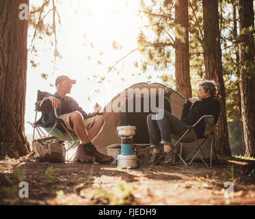 Portrait of mature couple sitting in chairs by tent at campsite. Senior man and woman relaxing and talking near - Stockfoto