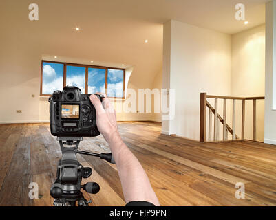 Hands holding a professional camera on tripod, about to take a shot of a modern interior with wooden floor - Stock Photo