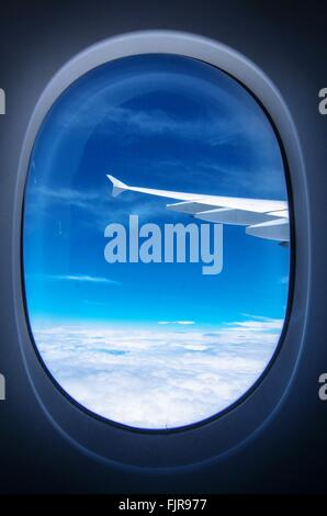 Cropped Image Of Airplane Flying Over Cloudscape Against Sky Seen Through Window - Stock Photo