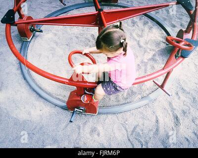 High Angle View Of Girl On Roundabout In Playground - Stockfoto