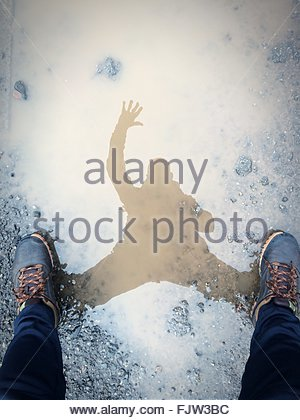 Low Section Of Person Reflection In Puddle - Stock Photo