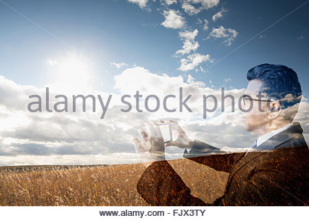 Digital composite businessman photographing golden wheat field - Stockfoto