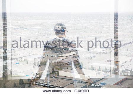 Digital composite businessman looking over industrial buildings - Stockfoto